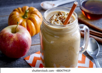 Fresh pumpkin coconut apple smoothie in mason jars garnished with toasted coconut and pecans sitting on orange chevron napkin surrounded by ingredients