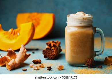 Fresh pumpkin spiced latte or coffee in cup decorated cinnamon on blue vintage background. Autumn, fall or winter hot drink. Cozy breakfast.