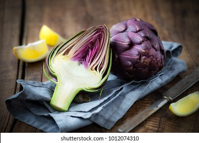 Fresh purple artichokes on dark rustic wooden background with slices of lemon