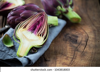 Fresh purple artichokes on dark rustic wooden background with slices of lemon with copy space for your text