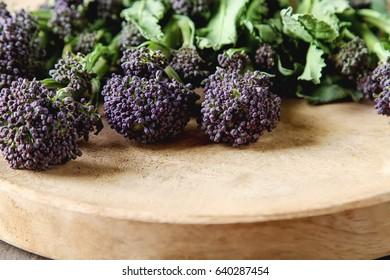 Fresh purple broccoli on a wooden plate. Vegan food. Dark background