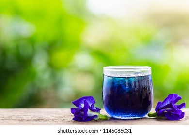 Fresh purple Butterfly pea or blue pea flower and juice in glass on wooden table background with green blur light space background for text, design, photo montage or advertising