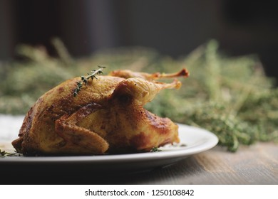 Fresh quail meat, quail eggs. Delicious fried quail with herbs and greens. Serving board with whole baked quails in a rustic wooden setting. Eggs quail and feathers in the shape of a nest