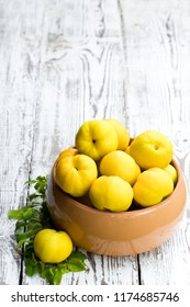Fresh  quince fruits on white wooden table