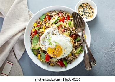Fresh quinoa tabbouleh salad with fried egg, tomatoes and cucumbers, healthy lunch bowl