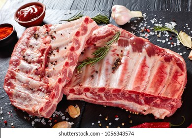fresh rack of raw pork spare ribs seasoned with spices on black slate tray with paprika, garlic cloves, bay leaves at background, vertical view from above, close-up
