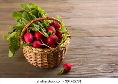 Fresh radishes in basket on wooden background