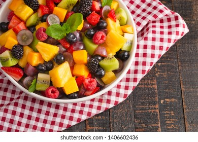 Fresh Rainbow Fruit Salad on a Wooden Table