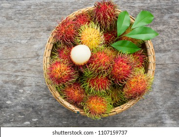 Fresh Rambutan in bamboo basket on wooden table background