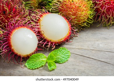 Fresh rambutan fruit and cross section showing the thick red skin and white flesh, Delicious rambutan sweet fruit aranged on wooden teble background, closeup, fruit in Thailand.