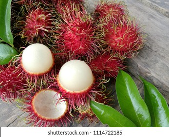 fresh rambutan isolate with green leaf. Fresh Rambutan in bamboo basket on wooden table background