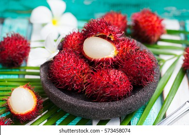 Fresh rambutans in a grey stone bowl on wooden colorful background.