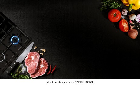 Fresh rare beef steak on a black stone with chef knife and cooking surface. With tomatoes, sweet and spicy peppers, greens and spices, white salt and black pepper.