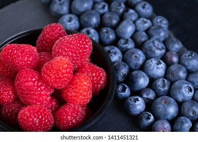 Fresh rasberries and blueberries on black stone plate