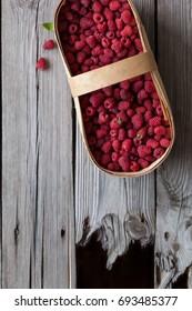 Fresh raspberries in basket over old wooden table
