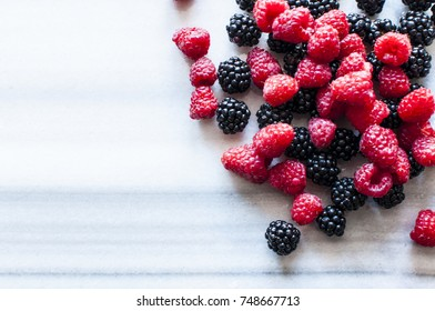 Fresh raspberries and blackberries on marble table, selective focus, close up, copy space