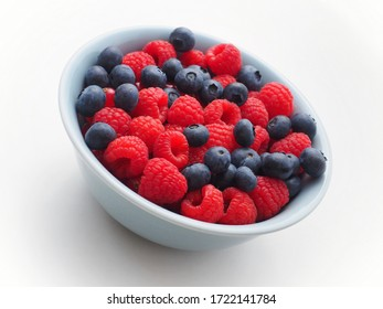 Fresh raspberries and blueberries in a bowl on white background