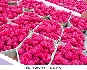 Fresh raspberries in boxes for sale.