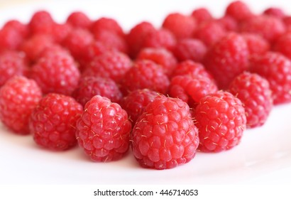 Fresh raspberries in heart shape on bright background