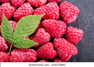 fresh raspberries with leaves as background, top view