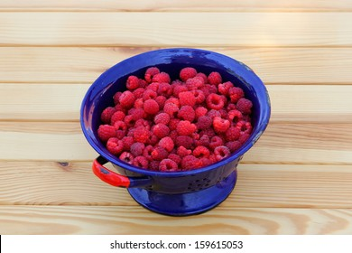 Fresh raspberries in an old seel enameled colander on a wooden table