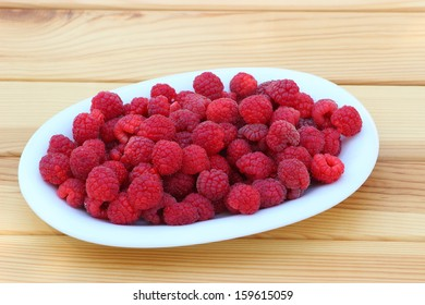 Fresh raspberries in an oval white plate on a wooden table