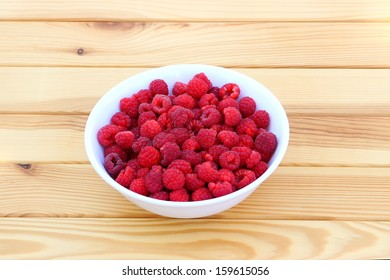 Fresh raspberries in a round white plate on a wooden table