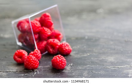 Fresh raspberries scattered on the wooden table