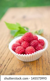 Fresh raspberries in small pot on wooden background
