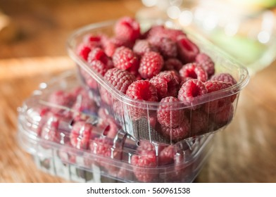 Fresh raspberry in plastic boxes from supermarket on kitchen table, berries in container, urban healthy life