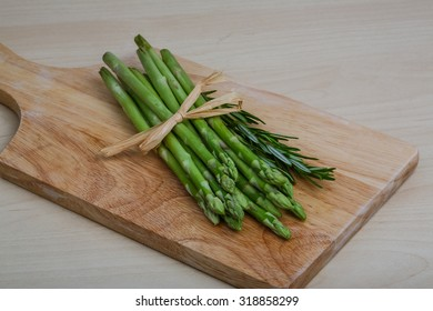 Fresh Raw asparagus heap on the wooden background