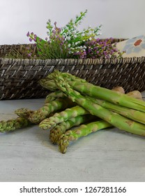 Fresh raw asparagus on kitchen surface with basket and flowers in the background. Stock Image.