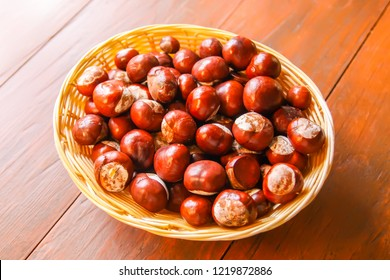 Fresh raw autumn chestnuts in a basket on wooden table. Aesculus hippocastanum.