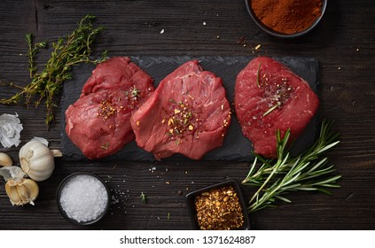 fresh raw beaf steak meat on dark wood kitchen table, top view