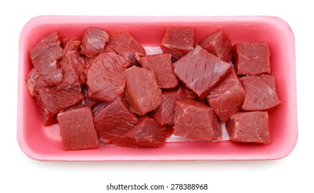 fresh raw beef cubes in tray on white background