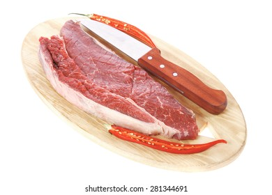 fresh raw beef fillet with red hot chili pepper and knife on wooden plate isolated over white background