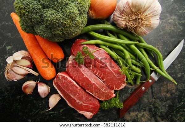 Fresh raw beef lamb fillet with other ingredients over marble stone chopping board