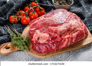 Fresh raw beef marbled steak. Chuck eye roll on a cleaver. Gray background. Top view