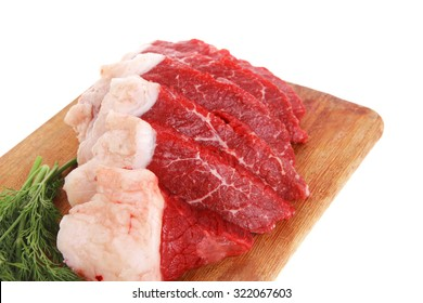 fresh raw beef meat steak slices on wooden cut board isolated over white background