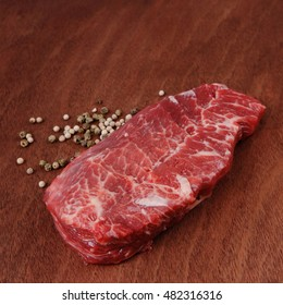 fresh raw beef meat steak with white and green peppercorn spice on walnut table