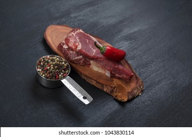 fresh raw beef piece fillet on small wooden plate with pepper peppercorns and nameplate space for text on black background