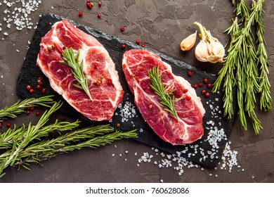 Fresh raw beef with rosemary on black background