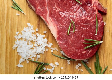 Fresh raw beef steak on wooden board with rosemary and sea salt. Top view.