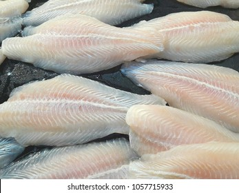 Fresh raw big pieces Pangasius dolly fish on counter. Fresh fish for sale in market.