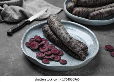 Fresh raw black carrots on grey plate