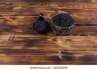 fresh raw black sturgeon hausen caviar in white crystal bowl on wooden background