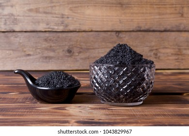 fresh raw black sturgeon hausen caviar in white crystal bowl on wooden background