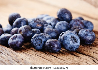 Fresh raw blueberries on wooden background close up