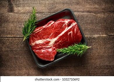 Fresh Raw braising steak on black tray with rosemary.