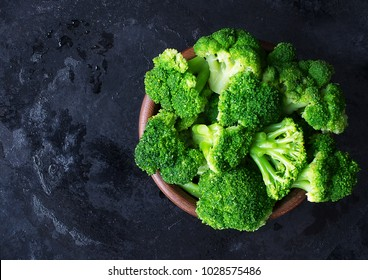 Fresh raw broccoli in a wooden bowl on a dark background